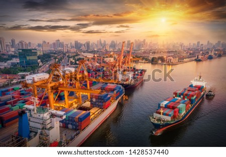 Logistics and transportation of Container Cargo ship and Cargo plane with working crane bridge in shipyard at sunrise, logistic import export and transport industry background #1428537440