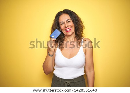 Middle age senior woman holding credit card over yellow isolated background with a happy face standing and smiling with a confident smile showing teeth