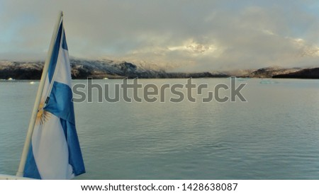 Argentina flag on a boat sailing on a lake with clouds and mountains in the background #1428638087