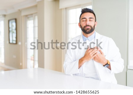Handsome hispanic doctor or therapist man wearing medical coat at the clinic smiling with hands on chest with closed eyes and grateful gesture on face. Health concept. #1428655625