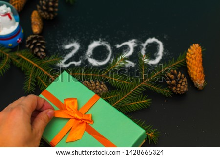 New year mood. Unties the ribbon on the gift box #1428665324