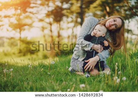 beautiful long-haired young mother in the summer sunshine park are sitting and playing with little cute sons #1428692834
