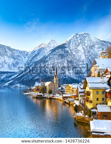 Classic postcard view of famous Hallstatt lakeside town in the Alps with traditional passenger ship on a beautiful cold sunny day with blue sky and clouds in winter, Salzkammergut region, Austria #1428736226