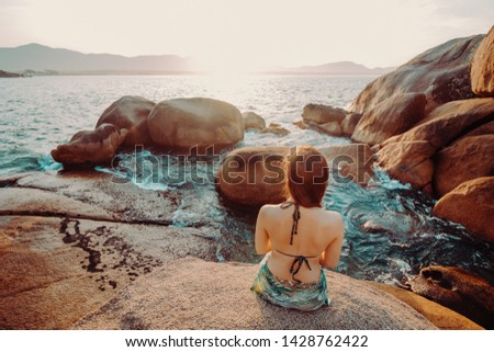 A girl looking at the sunset in the Natural Pools of Barra da Lagoa, in Florianopolis, Santa Catarina, Brazil. #1428762422