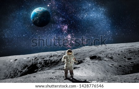 Moon surface with astronaut on it. Planet Earth on the background. Apollo space program. Elements of this image furnished by NASA. #1428776546