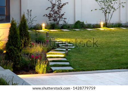 backyard of the mansion with a flowerbed and a lawn of green grass with a marble walkway of square tiles in the evening with a garden lighting with decorative ground lamps illuminating a warm light. #1428779759