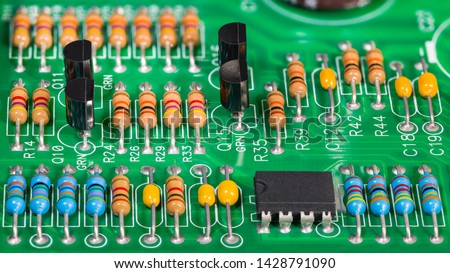 Colored electronic components. Resistors, transistors, capacitors and integrated circuit on PCB. Standard color code. Green copper board detail. Dismantled computer hardware. Electrotechnics, e-waste. #1428791090