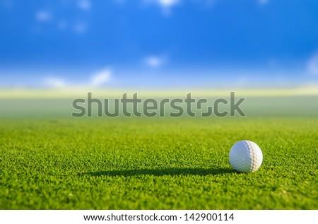 Golf ball on green grass with blur background
