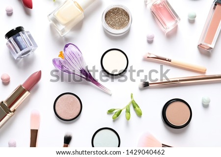 Different makeup products and flowers on white background, top view #1429040462