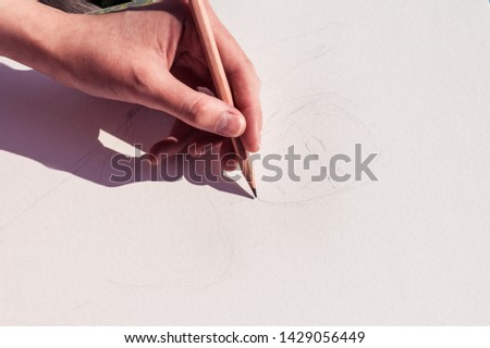 Girl artist draws a sketch with a pencil. Hand drawing. Drawing a portrait. Close-up #1429056449