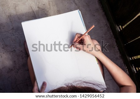Girl artist draws a sketch with a pencil. Hand drawing. Drawing a portrait.  #1429056452
