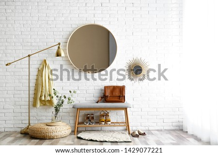 Hallway interior with big round mirror and shoe storage bench near brick wall Royalty-Free Stock Photo #1429077221