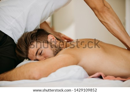 Male to male massage from young Asian therapist giving massage to muscle gym fit Caucasian man who laying on the bed in massage room. Remedial oil massage is performing on client. #1429109852