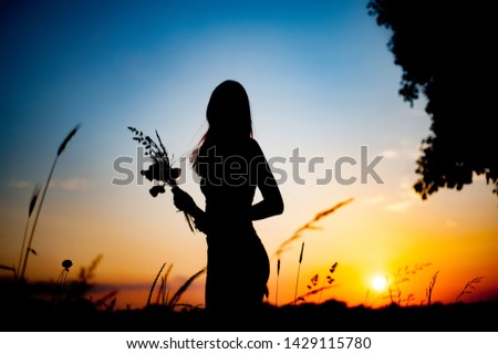 Silhouette of slim girl with a bouquet of flowers. girl stands at sunset in the field