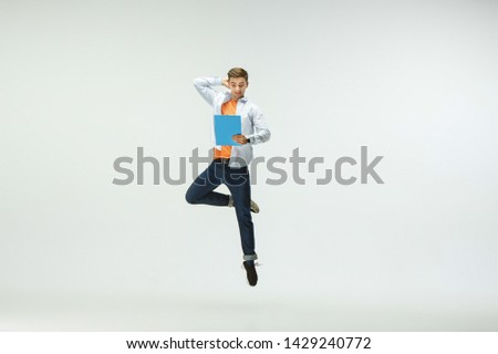 Happy young man working at office, jumping and dancing in casual clothes or suit isolated on white studio background. Business, start-up, working open-space, ballet or professional occupation concept. #1429240772