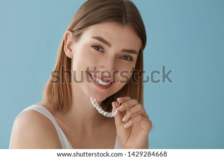 Teeth whitening. Woman with white smile, healthy straight teeth using clear removable braces, invisible teeth tray. Portrait of girl doing dental beauty treatment  #1429284668