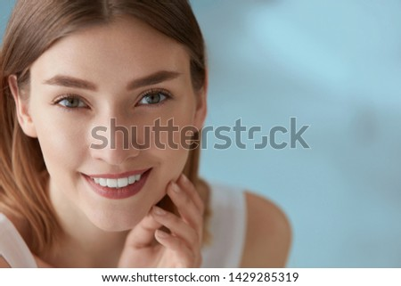 Beauty portrait of smiling woman with white teeth smile. Beautiful happy girl with fresh skin, natural face makeup indoors closeup #1429285319