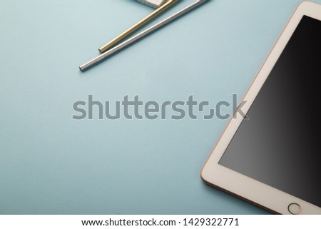 Tablet flat lay on blue background #1429322771