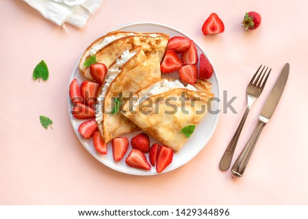 Crepes with ricotta cheese and fresh strawberries on pink pastel background, top view, copy space. Delicious crepes, thin pancakes. Royalty-Free Stock Photo #1429344896