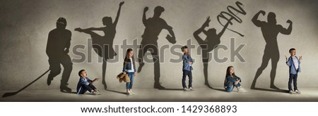 Childhood and dream about big and famous future. Conceptual image with boy and girl and shadows of fit athlete, hockey player, bodybuilder, ballerina. Creative collage made of 2 models. Royalty-Free Stock Photo #1429368893
