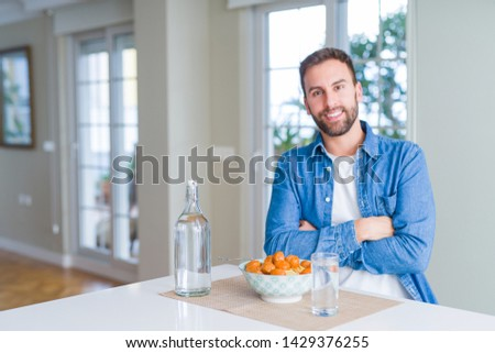 Handsome man eating pasta with meatballs and tomato sauce at home happy face smiling with crossed arms looking at the camera. Positive person. #1429376255