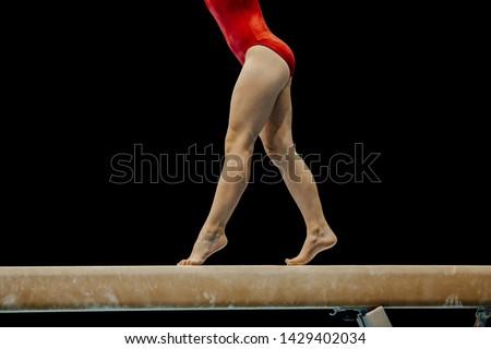 female gymnast in red leotard performance on balance beam on black background