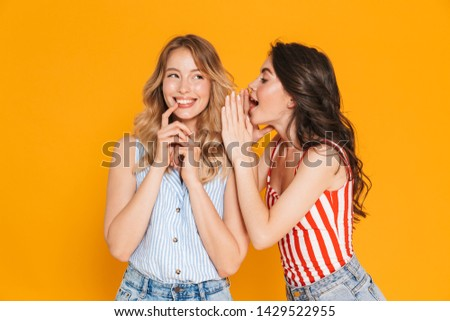 Portrait of two seductive blonde and brunette women 20s in summer wear expressing delight while whispering gossips isolated over yellow background #1429522955