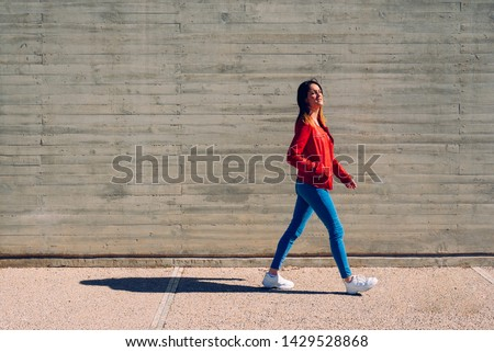 Millenial woman walking calmly in blue and red jeans next to a cement wall, gray background copy space. #1429528868