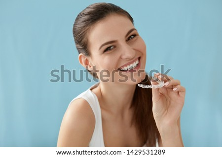 Dental care. Smiling woman with healthy teeth using removable clear braces aligner, orthodontic silicone trainer. Portrait girl with white smile using invisible whitening tray #1429531289