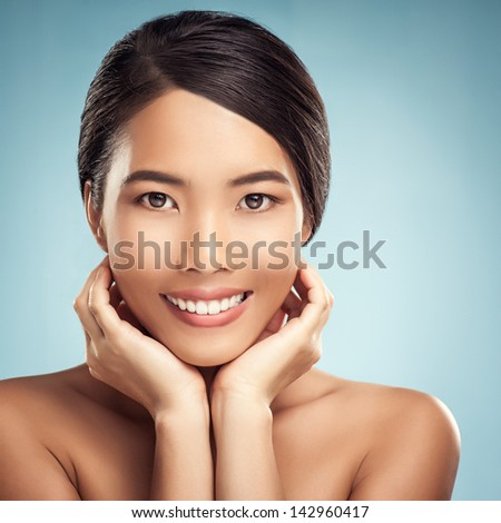 Portrait of a beautiful Asian woman smiling and gently touching her face. #142960417