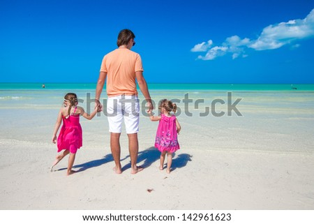 Rear view of young father and Rear view of young father and his two adorable daughters on an exotic vacation #142961623