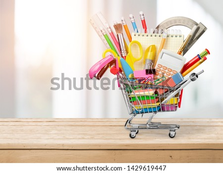 Stationery objects in mini supermarket cart on  background Royalty-Free Stock Photo #1429619447