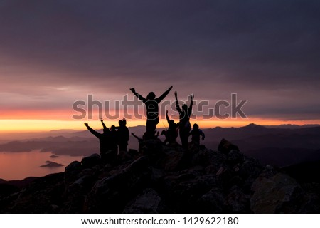 Multi-colored sunset. Silhouettes of people on top of a mountain overlooking the sea. #1429622180
