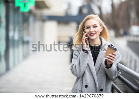 Cheerful young woman wearing pink coat using her phone in the sunny city street and drinking take away coffee in paper cup. #1429670879
