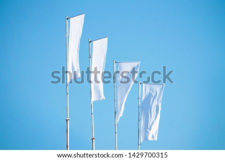 Three blank white flags on flagpoles against cloudy blue sky with perspective, corporate flag mockup to ad logo, text or symbol, company identity flag template with copy space #1429700315