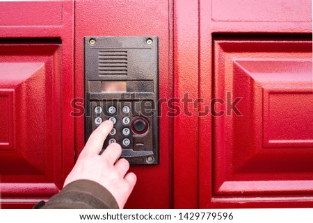 Male hand presses a button on doorbell and intercom. Traveling salesman ringing to the flat #1429779596