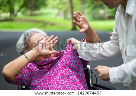 Asian elderly woman were physically abused ,attacking in outdoor park,angry young woman raised punishment fist,stop physical abuse senior people,caregiver,family stop violence and aggression concept Royalty-Free Stock Photo #1429874453