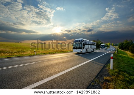 Two white buses traveling on the asphalt road in rural landscape at sunset with dramatic clouds                                #1429891862
