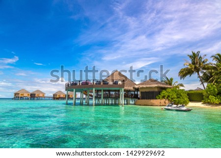 Water Villas (Bungalows) and wooden bridge at Tropical beach in the Maldives at summer day #1429929692