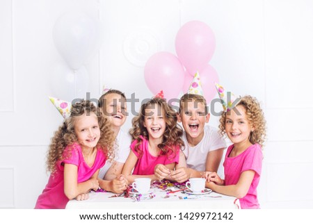 Happy beautiful cute kids smile at the holiday party with balloons and confetti together at the table in the white room #1429972142