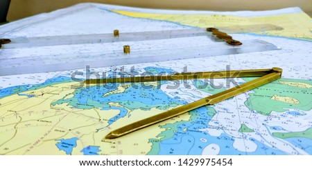 a table laid down with navigational chart compass divider and ruler for the purpose of navigation #1429975454
