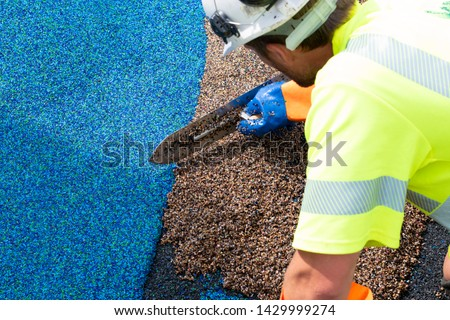 Man work at the side work. Construction side work. making a floor with the rubber beads on playground, New childrens playground under construction. Slide in the park playground. big plastic toy,  #1429999274