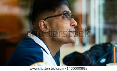 Young attractive Middle eastern male model drinks his coffee from behind the window glass at a local Chicago shop. the student ponders about the day while wearing trendy sunglasses in the Chicago area #1430000885