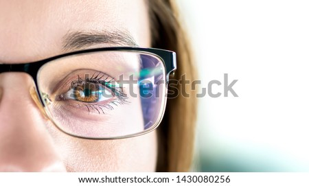 Close up of eye and woman wearing glasses. Optometry, myopia or laser surgery concept. Brown eyed girl with spectacles and eyeglasses. Macro portrait of face and specs. Light reflection on lens. Royalty-Free Stock Photo #1430080256
