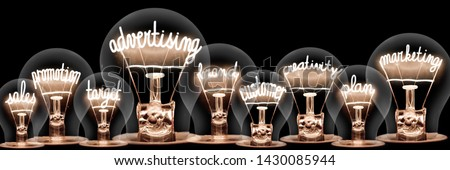 Group of light bulbs with shining fibers in a shape of Advertising, Marketing, Sales and Customer concept related words isolated on black background; horizontal composition #1430085944