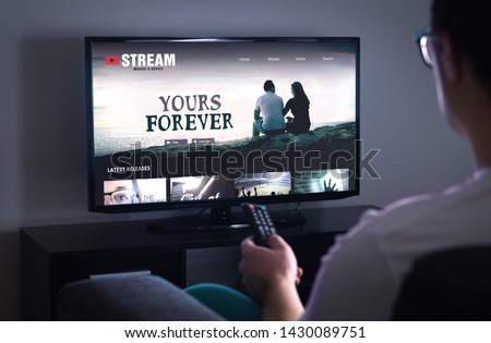 Online movie stream service in smart tv. Streaming series with on demand video (VOD) service in television. Man choosing film to watch with remote. Person sitting on couch at home late at night. #1430089751