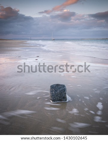 water swirling around a rock on a calm sandy beach at sunset  #1430102645