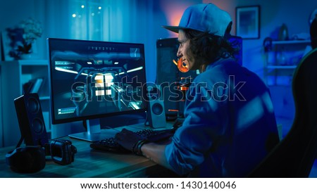 Professional Gamer Playing First-Person Shooter Online Video Game on His Powerful Personal Computer with Colorful Neon Led Lights. Young Man is Wearing a Cap. Living Room Lit in Low Key Style. Evening #1430140046