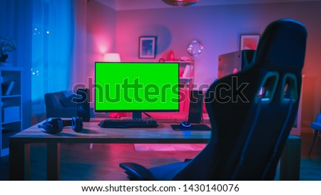 Powerful Personal Computer Gamer Rig with Mock Up Green Screen Monitor Stands on the Table at Home. Cozy Room with Modern Design is Lit with Pink Neon Light. #1430140076