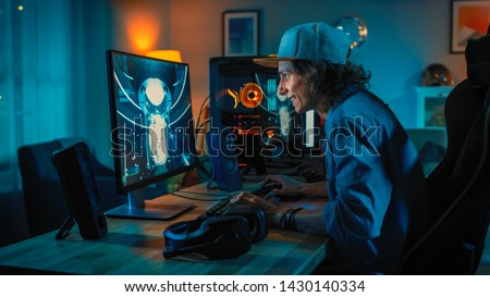 Professional Gamer Playing First-Person Shooter Online Video Game on His Powerful Personal Computer. Room and PC have Colorful Neon Led Lights. Young Man is Wearing a Cap. Cozy Evening at Home. #1430140334